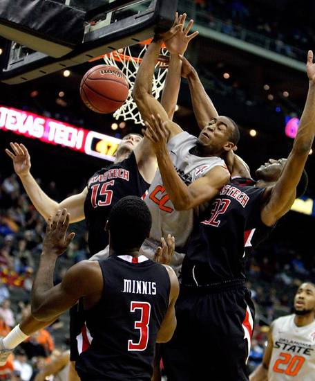 Oklahoma State's Markel Brown (22) fights for a rebound with Texas Tech's DeShon Minnis (3), Robert Lewandowski (15) and Jordan Tolbert (32) during the Big 12 tournament men's basketball game between the Oklahoma State Cowboys and the Texas Tech Red Raiders at the Sprint Center, Wednesday March 7, 2012. Photo by Sarah Phipps, The Oklahoman