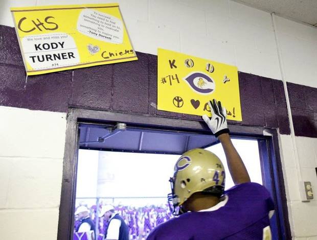 TJ Filer touches a poster honoring Kody Turner before running onto the field at the football game between Chickasha and Capitol Hill at Chickasha High School, Friday, Oct. 1, 2010, at the Bethany, Okla.  It was the first home game since the death of player Kody Turner. Photo by Sarah Phipps, The Oklahoman