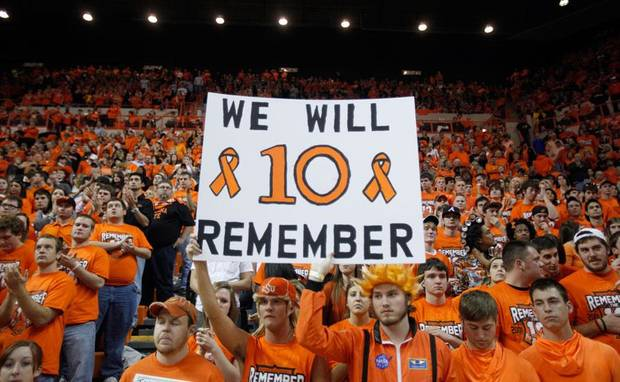 Fans hold a sign during a ceremony at halftime honoring the ten men who died in the OSU plane crash. Photo by Sarah Phipps, The Oklahoman