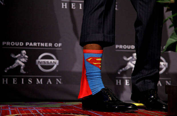 Heisman Trophy winner Robert Griffin III, of Baylor, shows off his Superman socks during a news conference after the ceremony, Saturday, Dec. 10, 2011, in New York. The junior quarterback known as RG3 became the first Heisman winner from Baylor. (AP Photo/Craig Ruttle) ORG XMIT: NYCR118