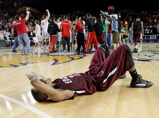 Edmond Memorial's James Woodard (3) lies on the court as the Union Redskins celebrate after the Class 6A boys high school basketball state tournament championship game between Edmond Memorial and Tulsa Union at the Mabee Center in Tulsa, Okla., Saturday, March 10, 2012. Union won, 37-36. Photo by Nate Billings, The Oklahoman