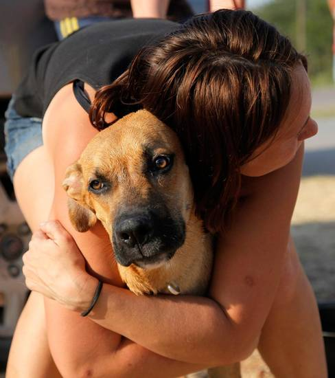 Ruth Hood hugs her dog Punky while waiting a gas station at SE 108th and Hwy 9 after evacuating her home near SE 132nd and Hwy 9 as a wildfire burning through Cleveland County near Norman, Okla., Friday, Aug. 3, 2012. Photo by Nate Billings, The Oklahoman
