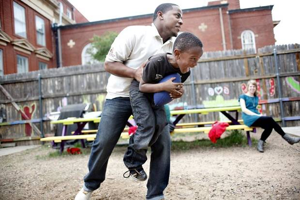 UNIVERSITY OF CENTRAL OKLAHOMA / CHILD / CHILDREN / KIDS: Andre Sparks with UCO's Kappa Alpha Psi fraternity tackles Michael Atako during a game of football at Positive Tomorrows, Wednesday, May 18, 2011. Photo by Sarah Phipps, The Oklahoman ORG XMIT: KOD