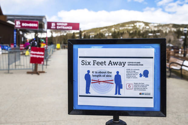 A sign near the Breckenridge Ski Resort gondola in Breckenridge, Colo., Saturday, March 14, 2020, outlines public health guidelines about social distancing to limit the spread of the new coronavirus. [Liz Copan/Summit Daily News via AP]