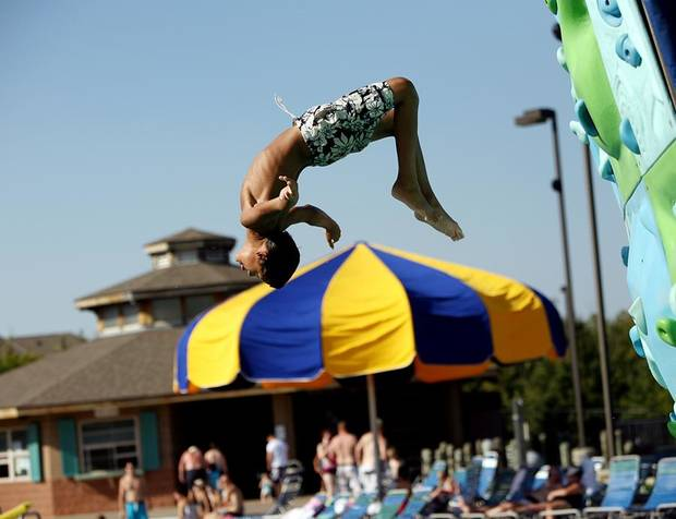 August Minter, 12, of Edmond, does a backflip off the rock wall during the last day of the season at Pelican Bay Aquatic Center in Edmond on Monday, Sept. 6, 2010. Photo by John Clanton, The Oklahoman ORG XMIT: KOD