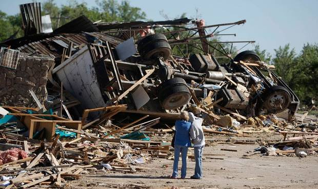 People stand by the remains of a business after a tornado struck Woodward, Okla., Sunday, April 15, 2012. Photo by Bryan Terry