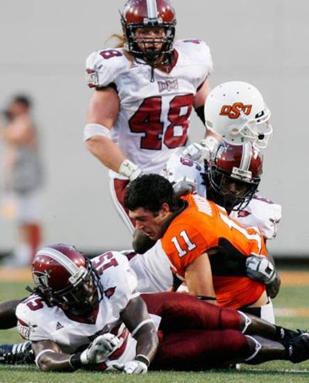 Zac Robinson's helmet flies off at the end of a run as he is sandwiched by defenders at the Oklahoma State University (OSU) college football game against Troy University (TU) Saturday, Sept 27, 2008 at Boone Pickens Stadium in Stillwater, Oklahoma. BY SARAH PHIPPS, THE OKLAHOMAN.