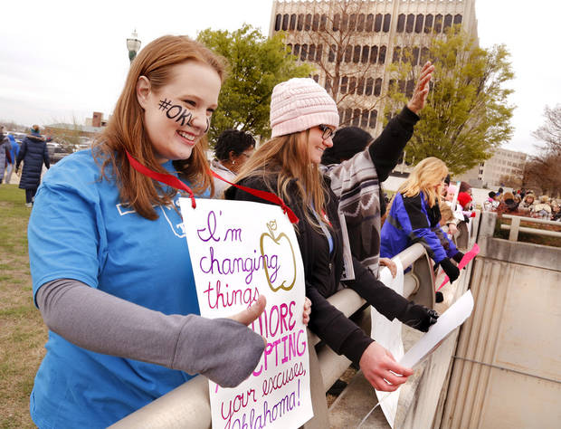 "Erin McMillan, nearest to camera, and Melissa Logan hold their signs while waving and giving ""thumbs up"" to drivers who honk their car horns in support of state teachers. McMillan and Logan are studying to receive degrees in teaching at the Early Childhood Education Institute at OU- Tulsa. They joined other teachers and supporters of education in standing on a walkway overlooking traffic on NE 23 Street. Teachers from throughout the state converged at the Capitol to bring their concerns about education funding to the attention of legislators and state officials during the first day of a statewide public schools teacher walkout  on Monday, April 2, 2018. Photo by Jim Beckel, The Oklahoman"