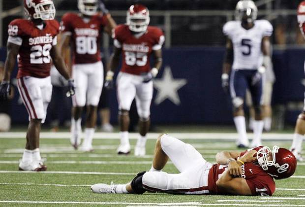 SHOULDER INJURY: OU quarterback Sam Bradford (14) lays on the turf after being injured late in the second quarter during the college football game between the Brigham Young University Cougars (BYU) and the University of Oklahoma Sooners (OU) at Cowboys Stadium in Arlington, Texas, Saturday, September 5, 2009. Bradford left the field after the play and did not return. BYU won, 14-13. By Nate Billings, The Oklahoman ORG XMIT: KOD