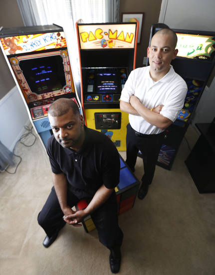 Mark Temple, left,  and Jose Rodriguez pose with 80's video games in Oklahoma City, Wednesday  August 21, 2013. Rodriguez and Temple are opening an 80's themed bar on NW 23. Photo By Steve Gooch, The Oklahoman