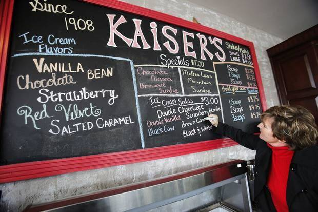 Kaiser's owners Angie Uselton works on the chalkboard menu.