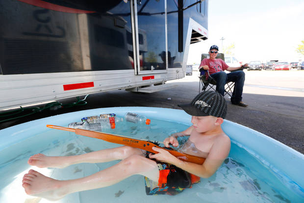 Cactus Barnes, 6, plays in a swimming pool as his big brother, Cutter Barnes,15, looks on during the International Finals Youth Rodeo at the Heart of Oklahoma Expo Center in Shawnee, Monday July 8, 2013. The Barnes' are from Maybell, Colorado, and set the pool up next to their horse trailer. Photo By Steve Gooch, The Oklahoman