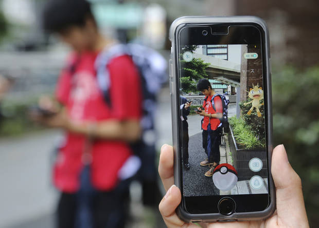 "FILE - In this July 22, 2016 file photo, Japanese students play ""Pokemon Go"" in the street as its released in Tokyo.(AP Photo/Koji Sasahara, File)"