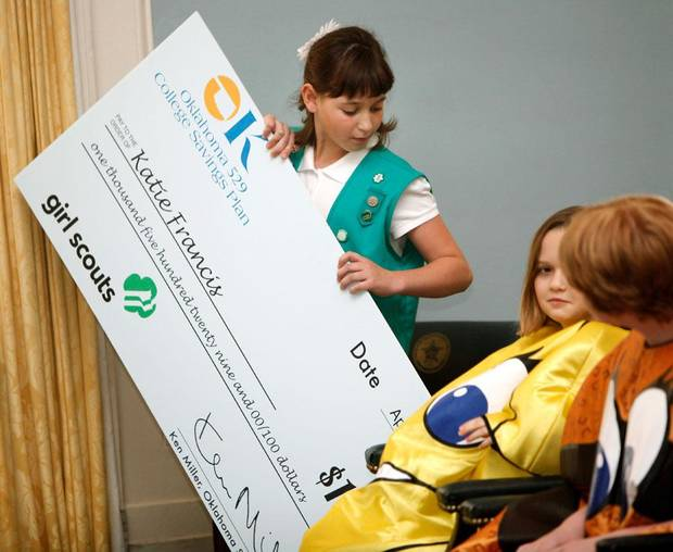 Katie Francis looks for a place to put a giant check given to her by State Treasurer Ken Miller after she was recognized for selling the most Girl Scout Cookies in the state this year, at the state Capitol in Oklahoma City, Thursday, April 12, 2012. Francis was awarded a $1,529 Oklahoma 529 College Savings Plan account for selling 7,482 boxes of cookies, an all-time state record. Photo by Nate Billings, The Oklahoman