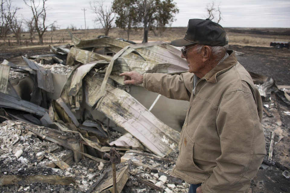 Photo -  Bill Zollinger, of Laverne, shows the rubble remaining of his childhood home after a wildfire swept through. [Photos by Ereich Tapia, For The Oklahoman]