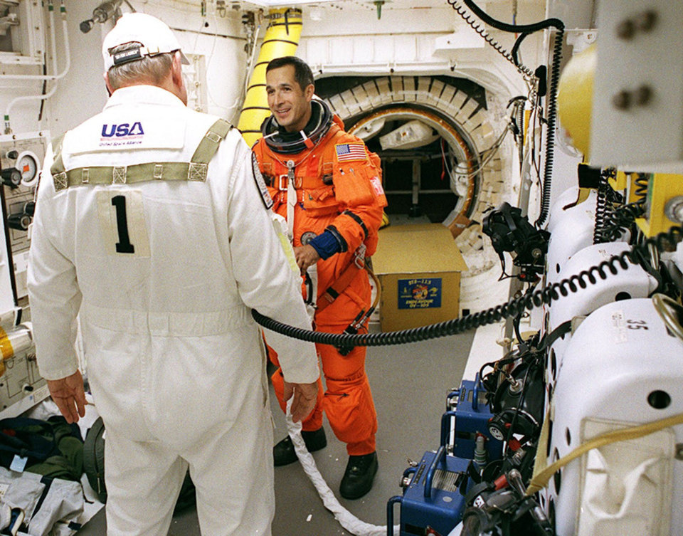 Photo - Commander John B. Herrington speaks to Rick Welty, Orbiter Closeout Crew chief for the STS-113 Endeavour mission to the International Space Station in 2002.  The photo is taken the in the White Room on the launch pad and the hatch you see behind Herrington is the entrance to the Space Shuttle Endeavour. Photo provided.
