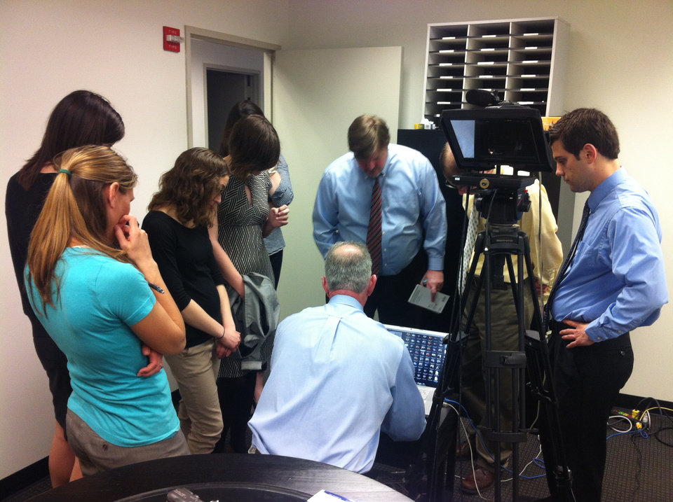Photo -  Chris Casteel shows reporters from the Washington Examiner some video clips.