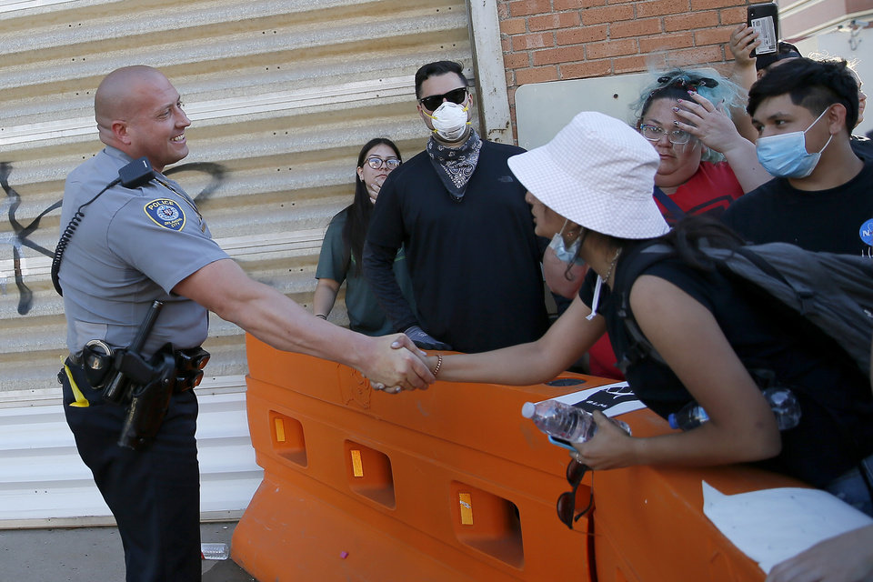 Photo - An Oklahoma City police officer shaes hands with a protester outside police headquarters in Oklahoma City on Sunday, May 31, 2020. The Black Lives Matter protest was in response to the death of George Floyd. [Bryan Terry/The Oklahoman]