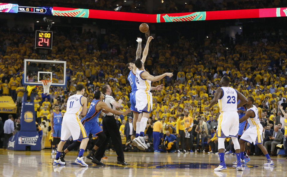 Photo - Oklahoma City's Steven Adams (12) and Golden State's Andrew Bogut (12) leap for the opening tip during Game 2 of the Western Conference finals in the NBA playoffs between the Oklahoma City Thunder and the Golden State Warriors at Oracle Arena in Oakland, Calif., Wednesday, May 18, 2016. Photo by Nate Billings, The Oklahoman