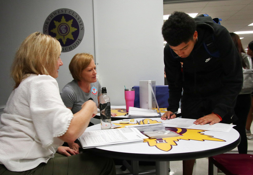 Photo - Marti Troy, left, and April Mays help student Gibson Knight, 18, with his registration form. Generation Citizen set up at Northwest Classen High School during lunch to register students age 17 and older to vote, Wednesday, September 25, 2019. [Doug Hoke/The Oklahoman]