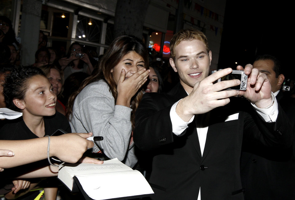 Photo - Actor Kellan Lutz takes photos with fans as he arrives at The Twilight Saga: New Moon premiere in Westwood, Calif. Monday, Nov. 16, 2009.  (AP Photo/Matt Sayles) ORG XMIT: CAGS121