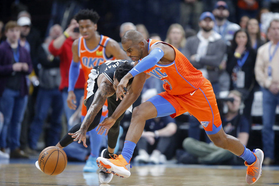 Photo - Oklahoma City's Chris Paul (3) goes for the ball beside San Antonio's Dejounte Murray (5) during an NBA basketball game between the Oklahoma City Thunder and the San Antonio Spurs at Chesapeake Energy Arena in Oklahoma City, Sunday, Feb. 23, 2020. [Bryan Terry/The Oklahoman]