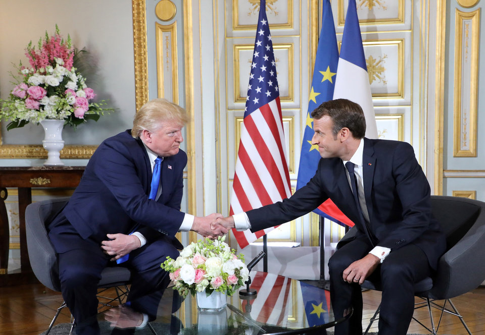 Photo - U.S President Donald Trump, left, shakes hands with French President Emmanuel Macron at the Prefecture of Caen, Normandy, France, Thursday, June 6, 2019. World leaders are gathered Thursday in France to mark the 75th anniversary of the D-Day landings. (Ludovic Marin/POOL via AP)