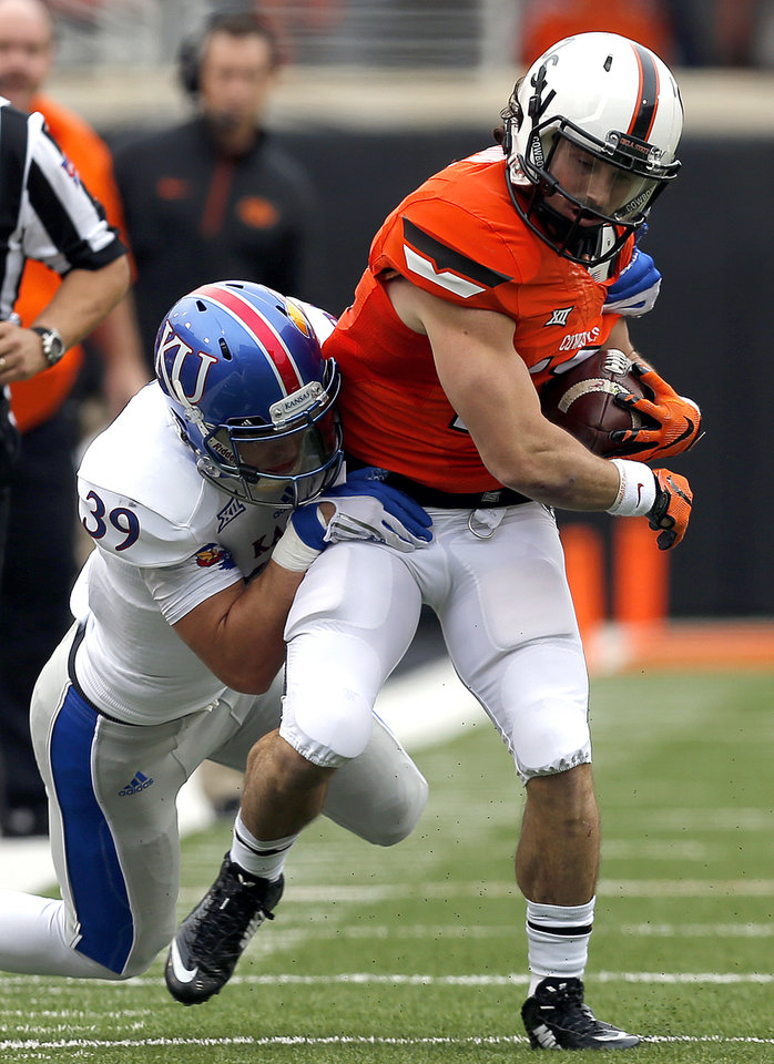 Photo - Oklahoma State's David Glidden (13) is brought down by Kansas' Michael Glatczak (39) during a college football game between the Oklahoma State University Cowboys (OSU) and the Kansas Jayhawks (KU) at Boone Pickens Stadium in Stillwater, Okla., Saturday, Oct. 24, 2015. Photo by Sarah Phipps, The Oklahoman