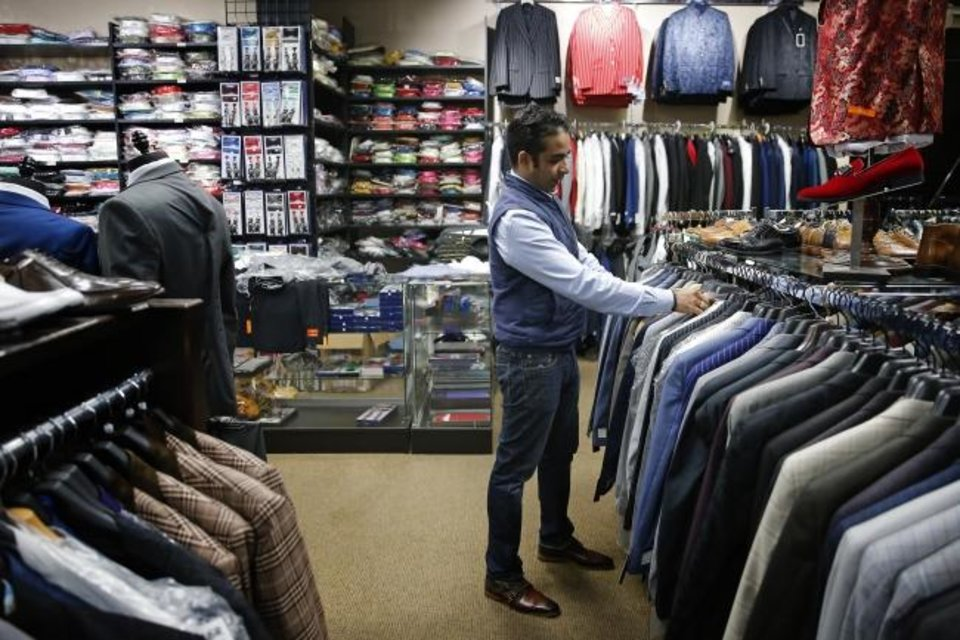Photo -  Andy Mahbubani, owner of GQ Fashions Fine Menswear, looks over inventory inside the store Thursday in preparation for its opening on Saturday. [BRYAN TERRY/THE OKLAHOMAN]