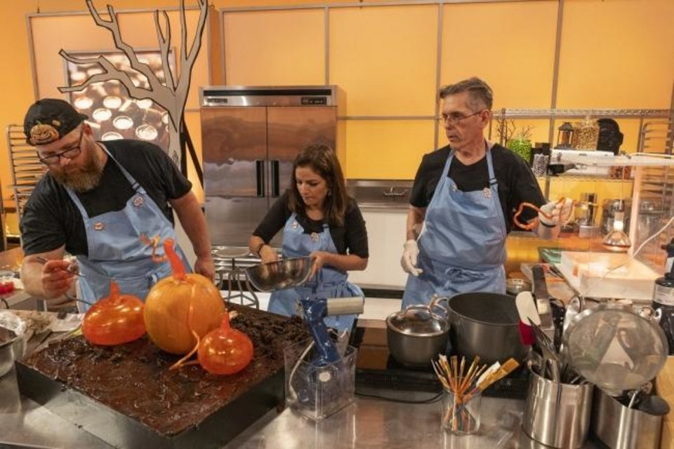 Photo -  From left, Team Mummies Rejects pumpkin carver Daniel Miller, Cake Maker Hemu Basu and Sugar Expert Steve Weiss working during Episode 1 of