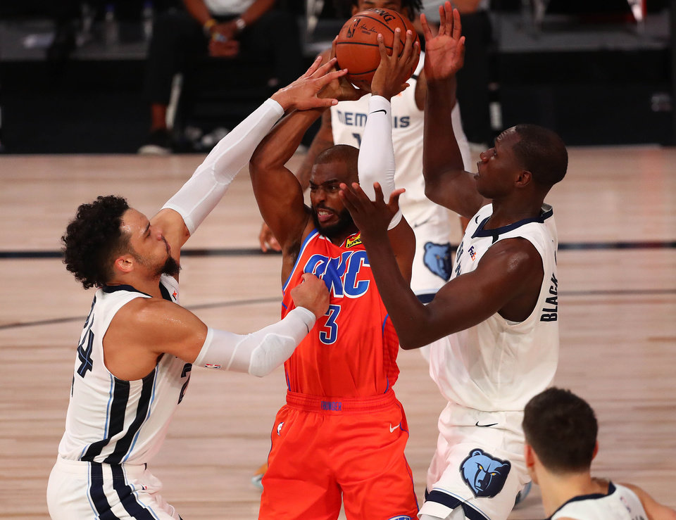 Photo - August 7, 2020; Lake Buena Vista, Florida, USA; Memphis Grizzlies center Gorgui Dieng (14) and guard Dillon Brooks (24) defend against Oklahoma City Thunder guard Chris Paul (3) during the first half of an NBA game at Visa Athletic Center. Mandatory Credit: Kim Klement-USA TODAY Sports