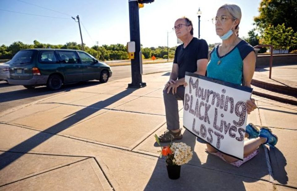 Photo -  Terry Fife and her husband, Ben Hardcastle, kneel on the corner of NE 23 and Martin Luther King Avenue. as morning traffic passes through the intersection. [Chris Landsberger/The Oklahoman]