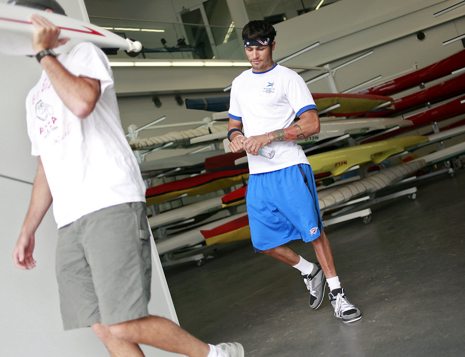 Photo - Paralympic Rower Tony Davis follows his coach Matt Muffelman (left) to the Oklahoma River as he starts a practice with rowing partner Jacqui Kapinowski in Oklahoma City on Tuesday, June 14, 2011. Photo by John Clanton, The Oklahoman