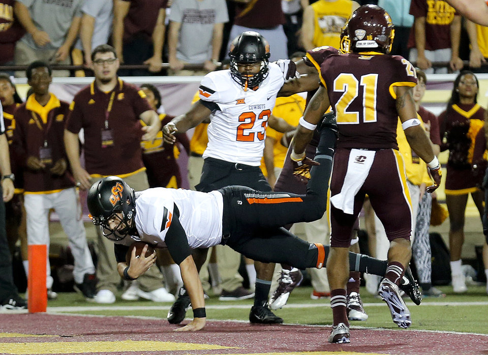 Photo - Oklahoma State's Mason Rudolph (2) dives in for a touchdown as Central Michigan's Stefon Armstead (16) looks on during the college football game between the Central Michigan Chippewas and the Oklahoma State University Cowboys at the Kelly/Shorts Stadium in Mount Pleasant, Mich., Thursday, Sept. 3, 2015. Photo by Sarah Phipps, The Oklahoman