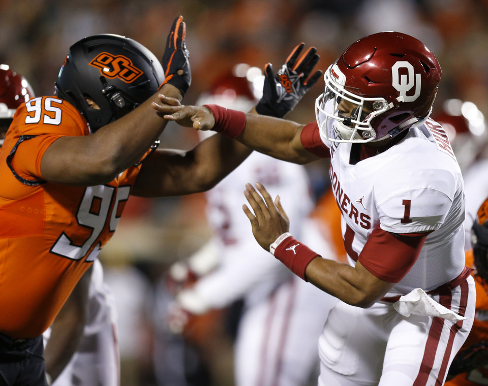 Photo - Oklahoma State's Israel Antwine (95) pressures Oklahoma's Jalen Hurts (1) in the first quarter during the Bedlam college football game between the Oklahoma State Cowboys (OSU) and Oklahoma Sooners (OU) at Boone Pickens Stadium in Stillwater, Okla., Saturday, Nov. 30, 2019. [Nate Billings/The Oklahoman]