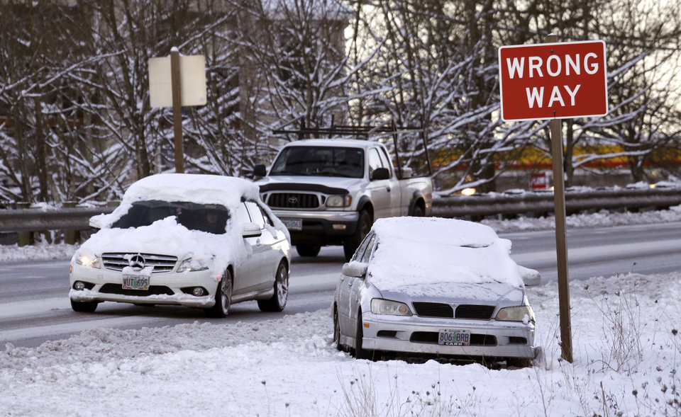 Photo - Motorists drive past a stranded car along Highway 99W in King City, Ore., Thursday, Jan. 12, 2017. Schools were closed and more than 5,000 Portland General Electric customers remained without power Thursday as the Portland, Ore., area recovers from a snowstorm. (AP Photo/Don Ryan)