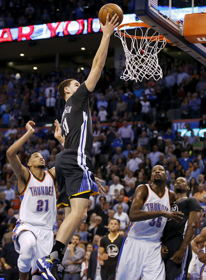 Photo - Golden State's Klay Thompson (11) lays up a shot past Oklahoma City's Andre Roberson (21) to put the Warriors within two points late in the fourth quarter as Oklahoma City's Kevin Durant (35) and Golden State's Harrison Barnes (40) looks on during an NBA basketball game between the Oklahoma City Thunder and the Golden State Warriors at Chesapeake Energy Arena in Oklahoma City, Saturday, Feb. 27, 2016. Golden State won 121-118 in overtime. Photo by Nate Billings, The Oklahoman