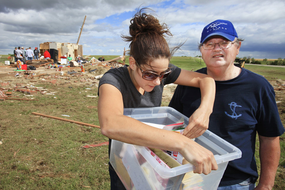 Photo - Tornado aftermath cleanup east of Piedmont, Wednesday, May 25, 2011.  Kelli Witte looks over a box of cards from her father, Mike Donovan, right, that was recovered from her house that was hit by Tuesdays tornado. Photo by David McDaniel, The Oklahoman