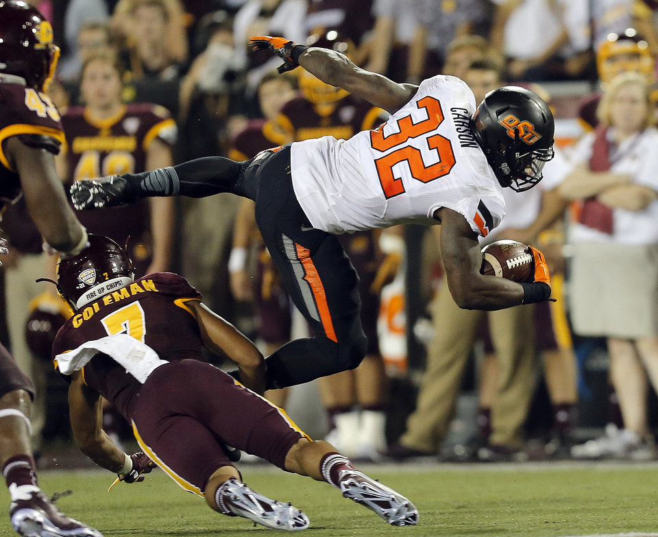 Photo - Oklahoma State's Chris Carson (32) is brought down by Central Michigan's Amari Coleman (7) during the college football game between the Central Michigan Chippewas and the Oklahoma State University Cowboys at the Kelly/Shorts Stadium in Mount Pleasant, Mich., Thursday, Sept. 3, 2015. Photo by Sarah Phipps, The Oklahoman