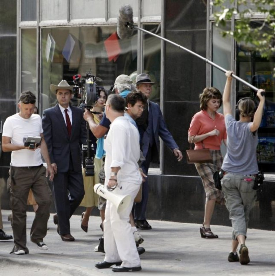 Photo -  Director Michael Winterbottom, left, and Casey Affleck, second from left, are surrounded by film and sound crews as they walk past downtown's First National Center during the 2009 filming of