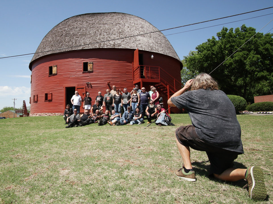 Photo -  A group of tourists from the Czech Republic pose for a group photo while visiting at the Round Barn on Route 66 in Arcadia. [Photo by Doug Hoke, The Oklahoman]