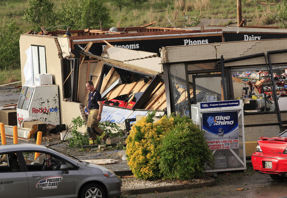 Photo - A firefighter walks out of the Love's store after a tornado ripped the building's roof off, causing its walls to collapse inward at the store,  south of Interstate 40 at Choctaw Rd., Monday evening, May 10, 2010.   Photo by Jim Beckel, The Oklahoman