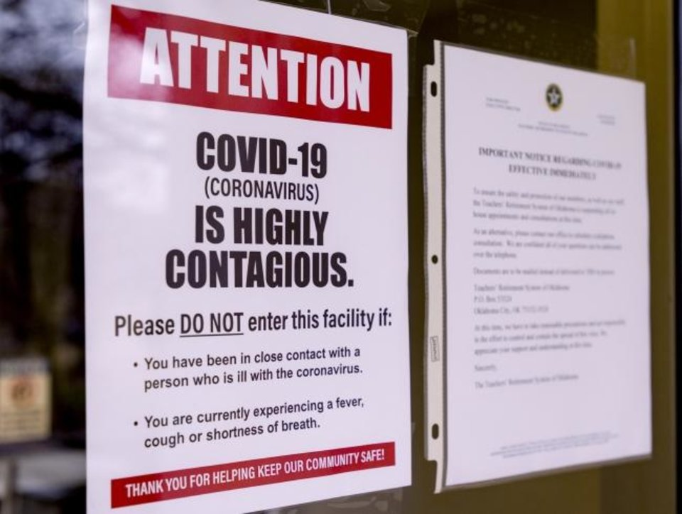 Photo -  Signs warning about the coronavirus are posted on the doors of the Oklahoma State Department of Education in Oklahoma City on Monday.  The Oklahoma State Board of Education voted to close all public schools in the state until April 6 to combat the spread of the coronavirus.  [Chris Landsberger/The Oklahoman]