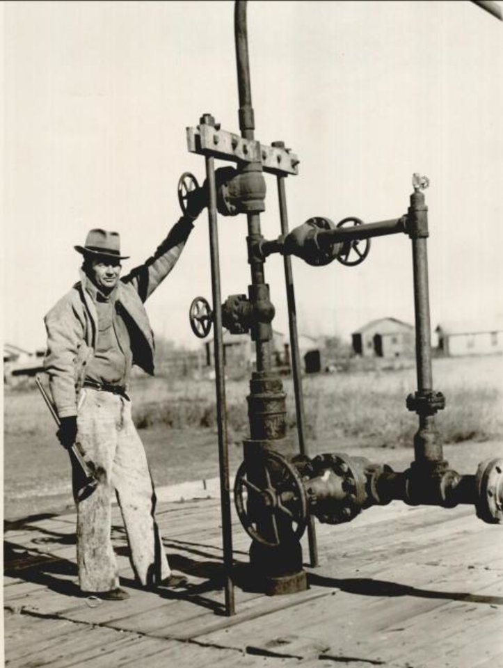 Photo -  A worker is pictured at the discovery well for the Oklahoma City Field in 1936. Overproduction from wells prompted Oklahoma's Legislature to approve statutes during that decade that enabled the Corporation Commission to set production limits on wells to conserve natural resources, protect public safety and encourage economic development. [THE OKLAHOMAN ARCHIVES]