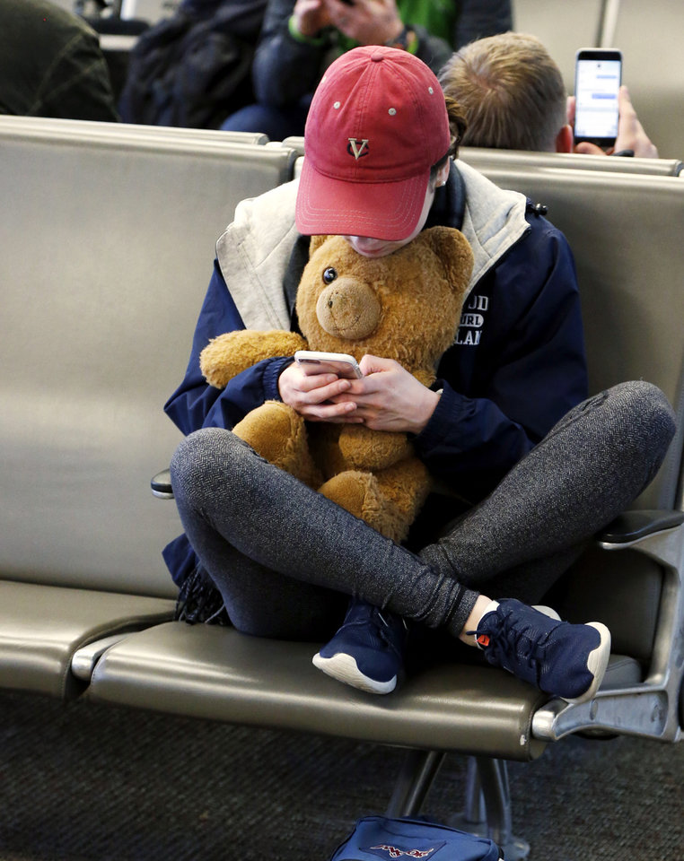 Photo -  Megan Wilson, an Oklahoma City University freshman from Santa Barbara, Calif., waits to board her flight Thursday as holiday travelers pass through Will Rogers World Airport. She is accompanied by her well-traveled bear, Alfonso. [Photo by Steve Sisney, The Oklahoman]