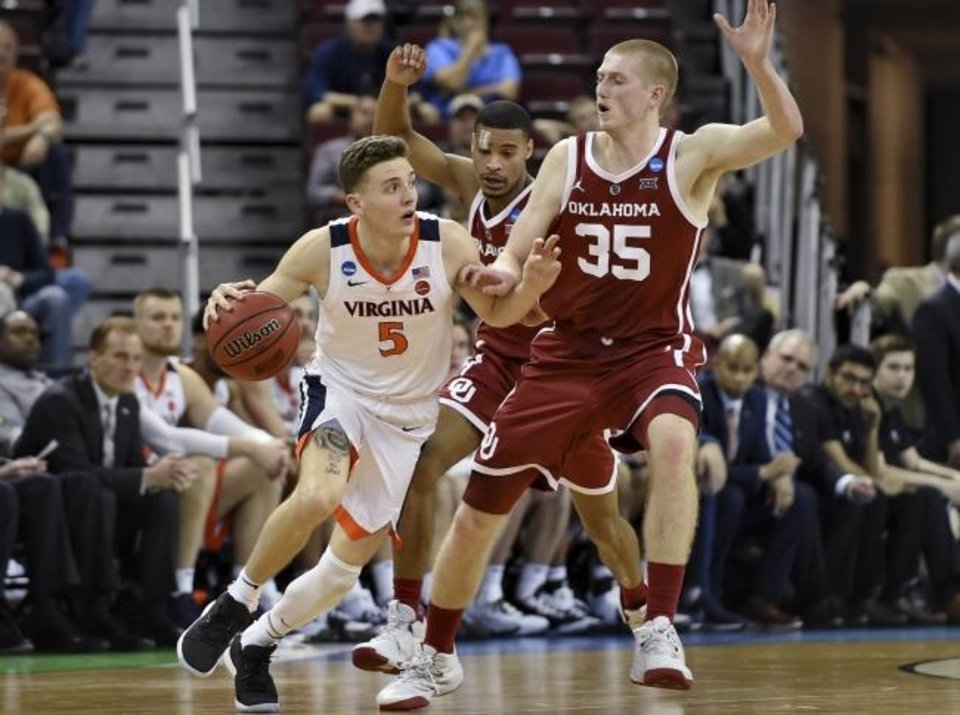 Photo -  Virginia's Kyle Guy, left, drives against Oklahoma's Brady Manek during the second half of Sunday's game in the NCAA Tournament in Columbia, S.C. Virgina beat the Sooners, 63-51. [AP Photo/Richard Shiro]