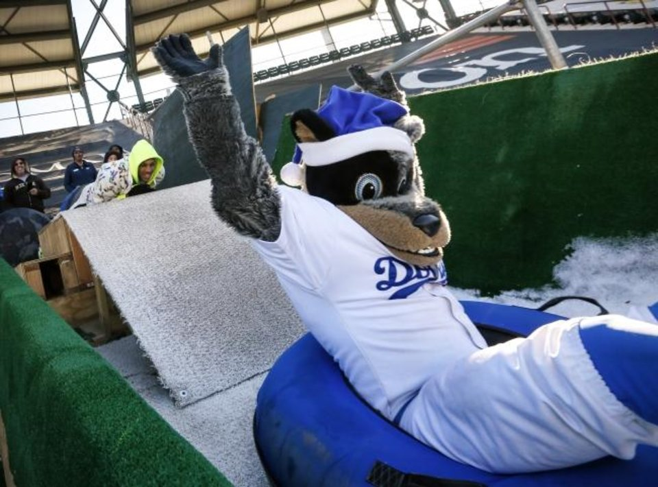 Photo -  Oklahoma City Thunder player Darius Bazley, left, watches Oklahoma City Dodgers mascot Brix snow tube after giving him a push to get started during a visit by Thunder basketball players to the LifeShare WinterFest at Chickasaw Bricktown Ballpark in Oklahoma City, Monday, Dec. 30, 2019. [Nate Billings/The Oklahoman]