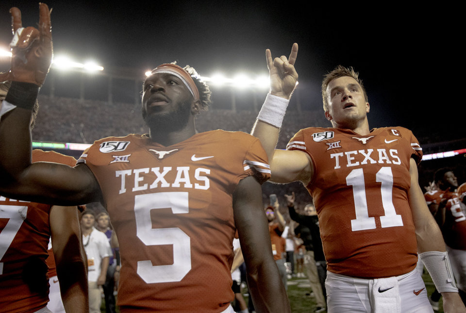 "Photo - Texas defensive back D'Shawn Jamison (5) and quarterback Sam Ehlinger (11) hold up the ""Hook 'em Horns"" sign for the playing of ""The Eyes of Texas"" following Texas' 36-30 win over Oklahoma State during an NCAA college football game Saturday, Sept. 21, 2019, in Austin, Texas. (Nick Wagner/Austin American-Statesman via AP)"