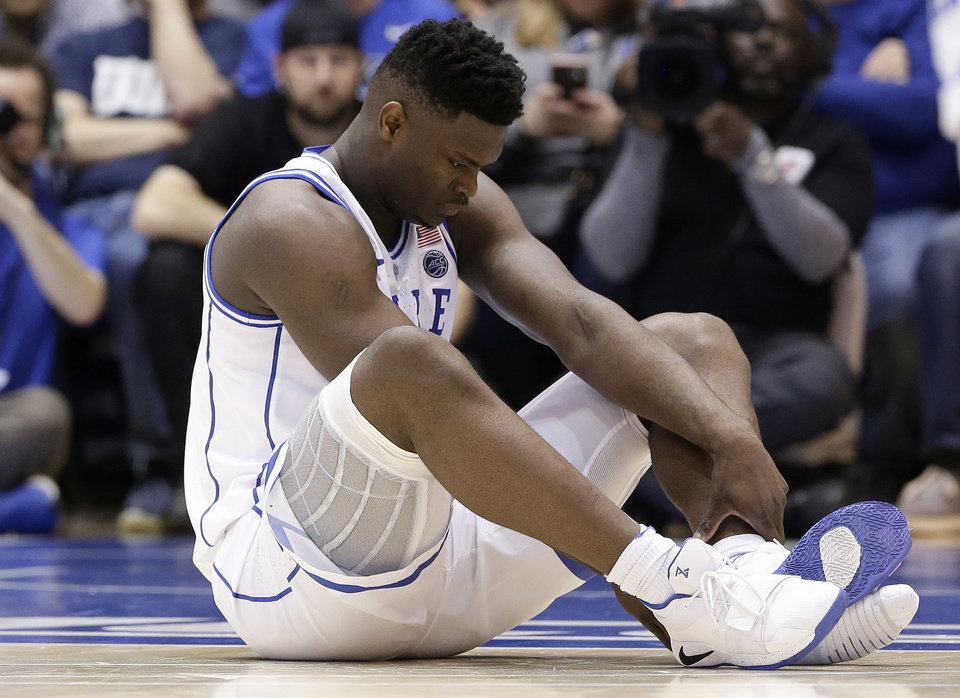 Photo - Duke's Zion Williamson sits on the floor following a injury during the first half of an NCAA college basketball game against North Carolina, in Durham, N.C., Wednesday, Feb. 20, 2019. Duke might have to figure out what the Zion Show will look like without its namesake. All because of a freak injury to arguably the most exciting player in college basketball. As his Nike shoe blew out, Williamson sprained his right knee on the first possession of what became top-ranked Duke's 88-72 loss to No. 8 North Carolina.(AP Photo/Gerry Broome)