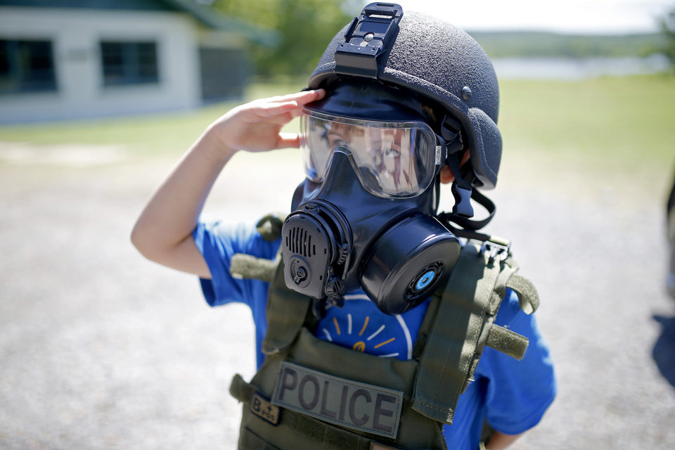 Photo -  Bryden salutes after trying on police tactical gear June 21 during Camp Hope in Chouteau. The camp is for children who have experienced trauma. [Photo by Sarah Phipps, The Oklahoman]